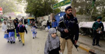 Following the murder of 132 schoolchildren and nine adults in an army school in Peshawar, the government has pledged to increase surveillance in schools. Here, schoolchildren walk alongside police in Pakistan. Image credit: Flickr (Jordi Bernabeu Farrús) Creative Commons.