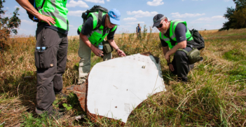 A Dutch and an Australian Police officer investigate the scene of the MH17 crash. Photo Credit: Wikimedia Commons (Dutch Department of Defence) Creative Commons.