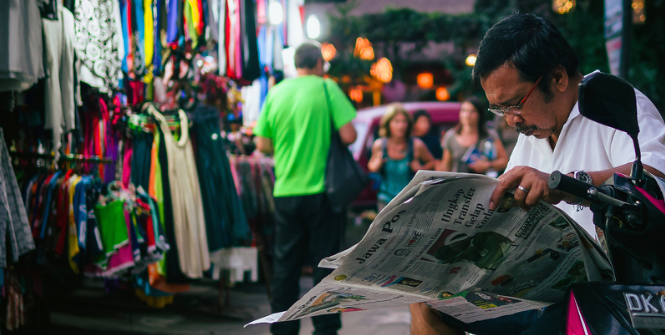 A Man reads an Indonesian Newspaper on the street. Photo Credit: Flickr (Just Call Me Mo) Creative Commons.