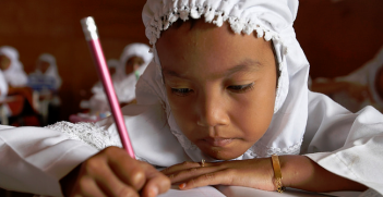 Schoolchildren write at their desk at a school in Indonesia. Photo Credit: Flickr (DFATD   MAECD) Creative Commons