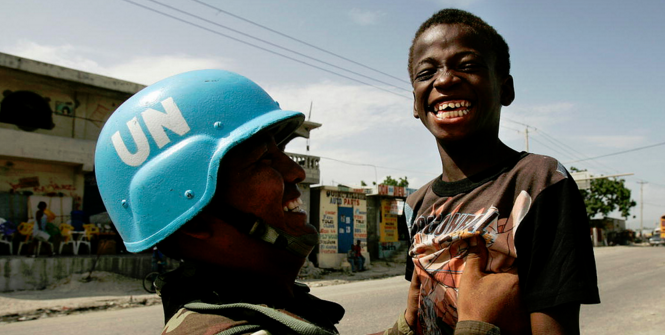 A Bolivian UN peacekeeper playfully picks up a Haitian boy at a checkpoint in Cité Soleil. Photo Credit: Flickr (United Nations Photo) Creative Commons