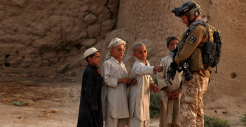 Australian press photographer, Gary Ramage shows his equipment to local Afghan children while on patrol in Dand District with Royal Air Force II Squadron troops, June 26, 2010, Dand District, Kandahar, Afghanistan. Photo source: Kenny Holston (Flickr). Creative Commons.