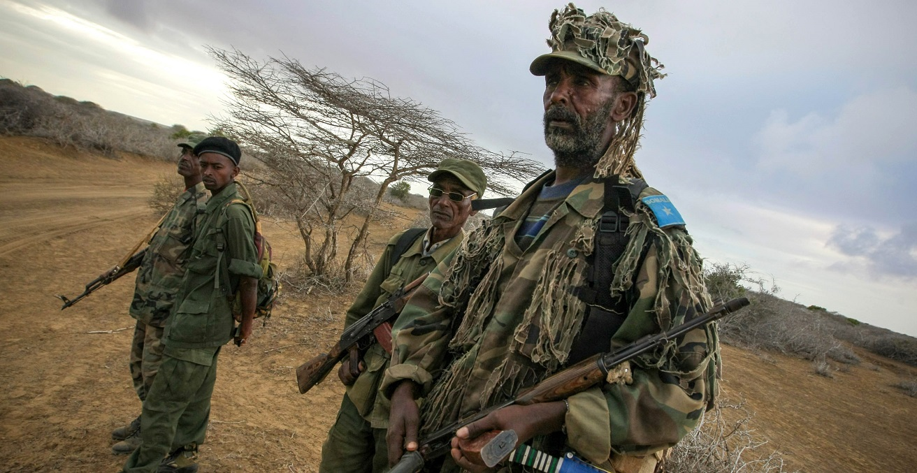 Soldiers of the Somali National Army watch from the roadside as a convoy carrying troops begins an advance on the Somali port city of Kismayo