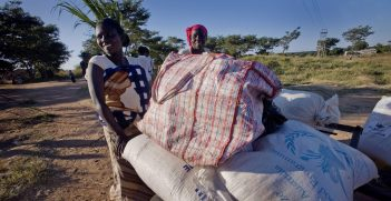 Women carry their village's food aid from Australia in a cart.