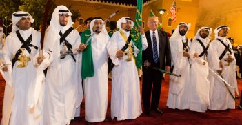 President Donald Trump poses for photos with ceremonial swordsmen on his arrival in Saudi Arabia.