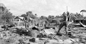 Australian troops examine the ashes and rubble in Long Dien after the Tet Offensive in February 1968. © Commonwealth of Australia (Department of Veterans' Affairs)