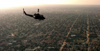 A US UH-1N Huey helicopter flew over Mogadishu on a patrol mission to look for signs of hostilities, 1 December 1992 (Credit: US Department of Defense).