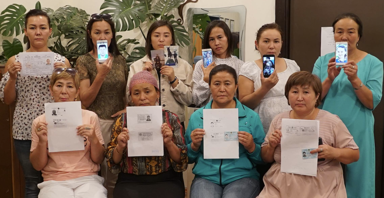 Uyghur women hold up pictures of their detained relatives. Source: Amnesty International