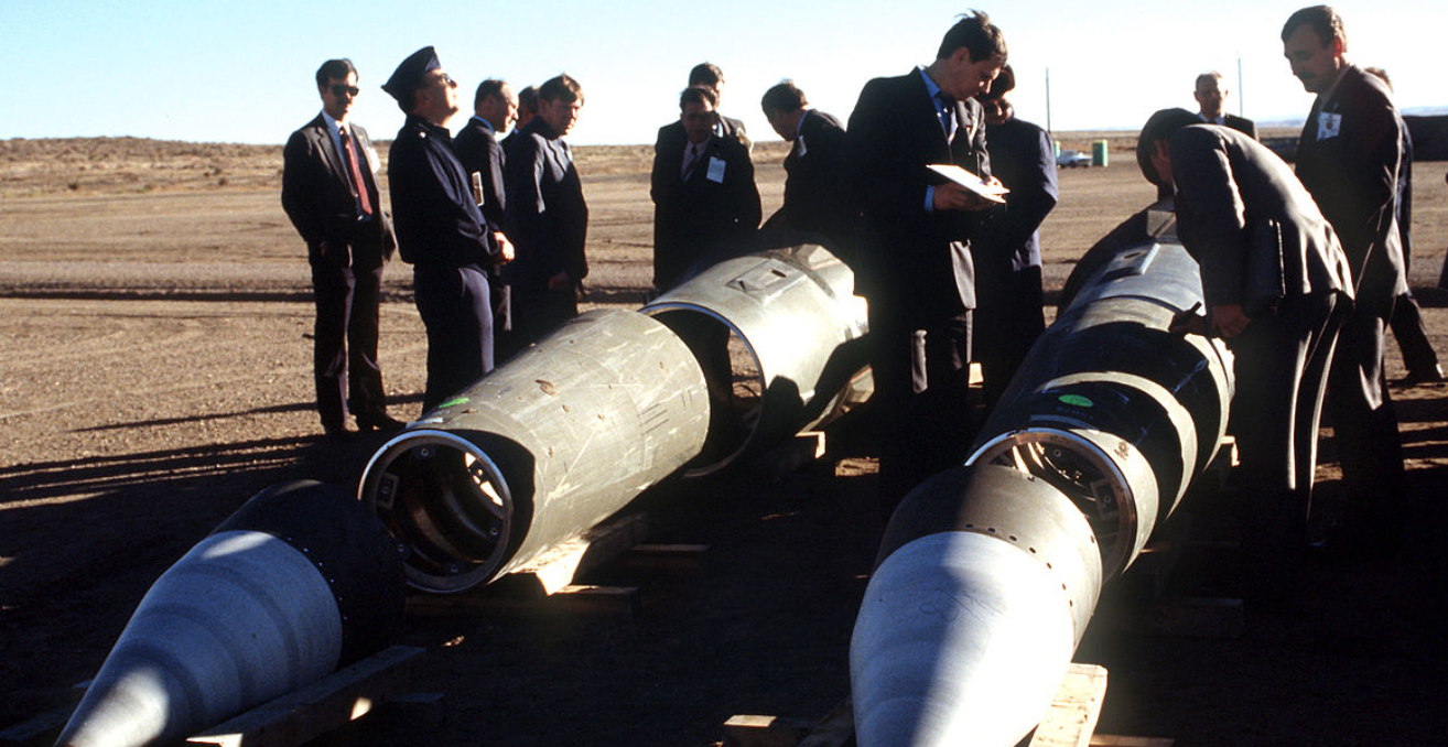Soviet inspectors and their American escorts stand among several dismantled Pershing II missiles as they view the destruction of other missile components. The missiles are being destroyed in accordance with the Intermediate-Range Nuclear Forces (INF) Treaty. source: Wikimedia Commons