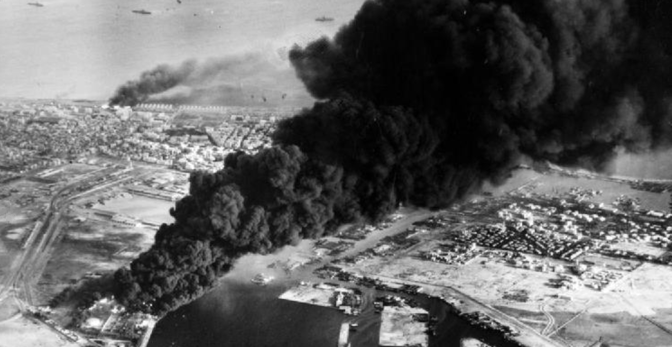 Smoke rises from oil tanks beside the Suez Canal hit during the initial Anglo-French assault on Port Said, 5 November 1956. Photograph MH 23509 from the collections of the Imperial War Museums