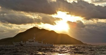 A Coast Guard patrol vessel passes by Uotsuri, the largest island in the Senkaku/Diaoyu chain. Now uninhabited, it used to be home to 248 Japanese, in a community of 99 houses in the late 1890s. They were mostly employed working in a Bonito flake factory on the island. Photo by Al Jazeera English. Source: https://bit.ly/2Ldgfbh