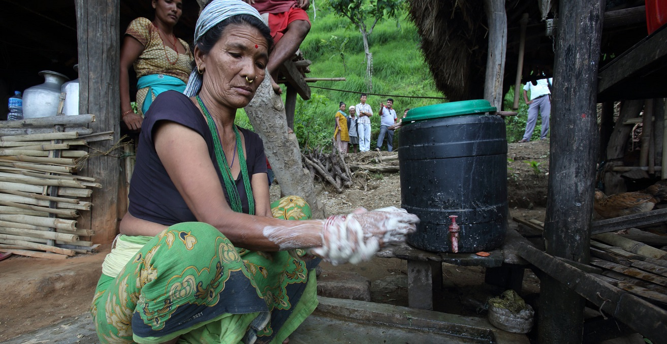 Woman washes her hands using water collected from the village gravity flow taps at a NEWAH WASH water project in Puware Shikhar, Udayapur District, Nepal. Source: Jim Holmes/AusAID https://bit.ly/351OawC