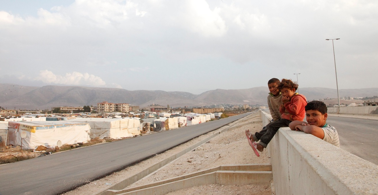 Syrian refugee children sit on a wall overlooking an 'informal tented settlement' in Lebanon's Bekaa valley. The mountains in the background form the border with Syria. Source: Russell Watkins/Department for International Development https://bit.ly/3bLatIm