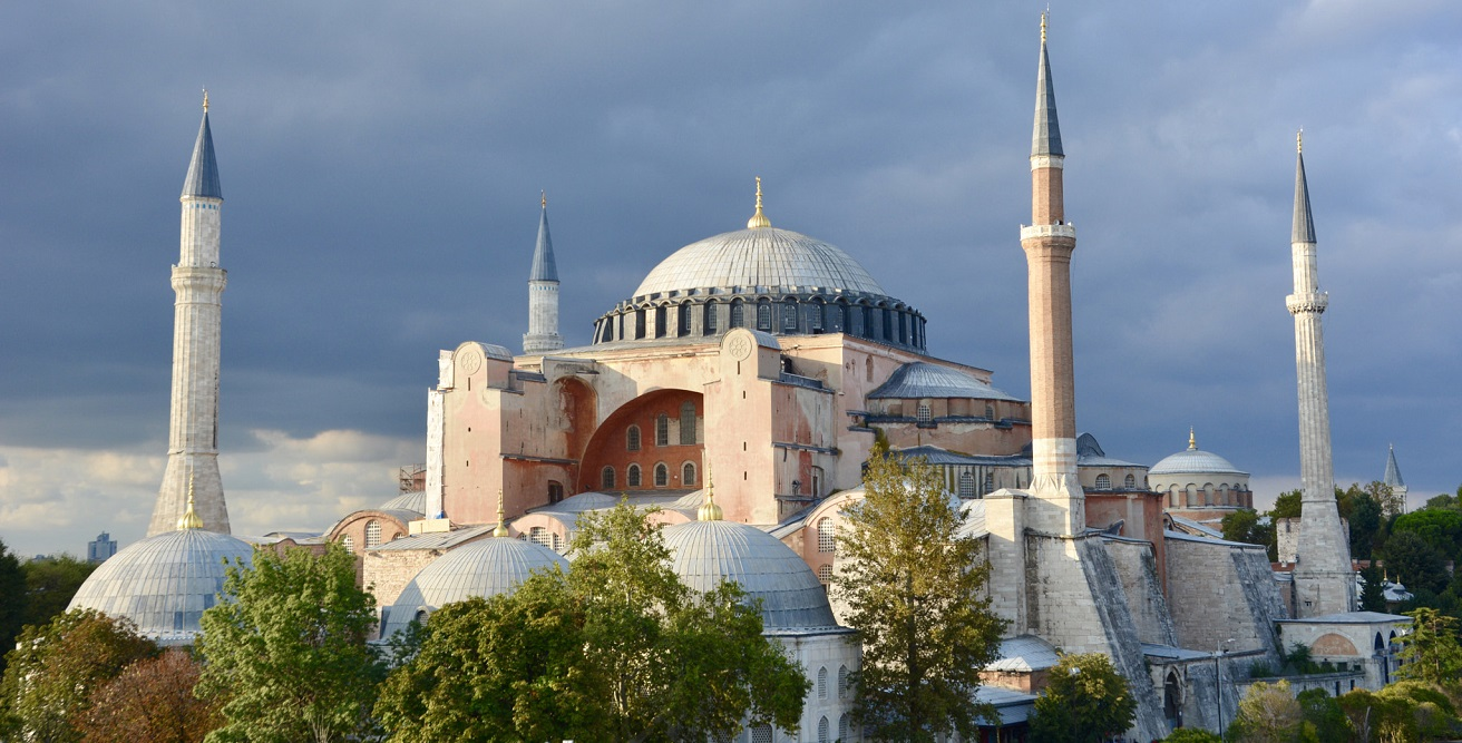 A photo of the Hagia Sophia surrounded by trees and dark clouds. Source: Adli Wahid https://bit.ly/32eHjAr
