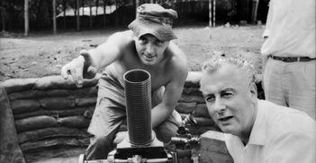 Phuoc Tuy Province, Vietnam. 1966-08. Mortar lesson for the Deputy Leader of the Federal Opposition, Mr Gough Whitlam, as he listens to one of his constituents, Lance Corporal Walter Jenkins of Warwick Farm, Sydney, NSW (left), in the mortar pit at the 5th Battalion, The Royal Australian Regiment (5RAR), during an inspection of 1st Australian Task Force installations. Image credit: Australian War Memorial Collections