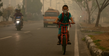 A student goes to school wearing a mask to protect him from the smoke that blankets the city of Palangka Raya, Central Kalimantan. Photo Source (Flickr) CIFOR. Creative Commons.