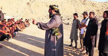 Sheikh armed with knife & pistol teaches with outstretched index recruits in IS-Boot-Camp. Screen shot of IS traning video provided by quapan (Flickr). Creative Commons.