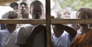 Young Liberians listen outside a women's peace hut in Totoa, Bong County, Liberia. 7 March 2011. Photo Source: UN Photo/Staton Winter.