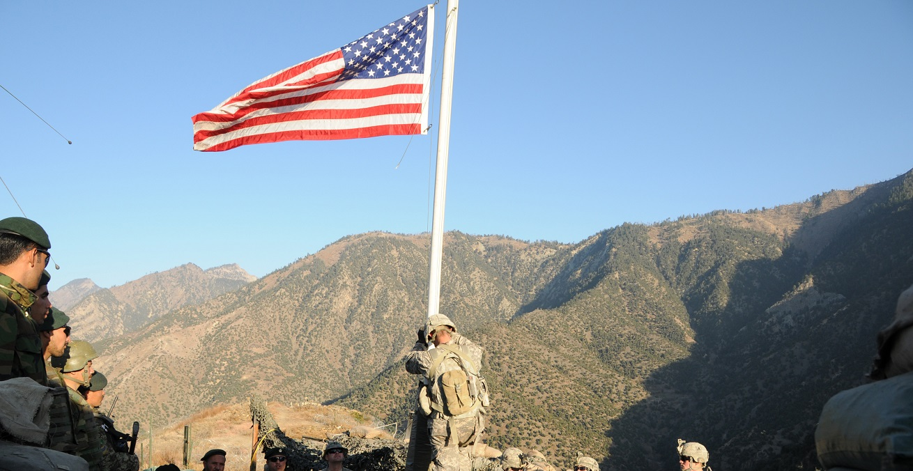 A noncommissioned officer with Troop C, 1st Squadron, 32nd Cavalary Regiment, prepares to lower the American flag during a transfer of authority ceremony at Observation Post Mace, as U.S. and Afghan National Army Soldiers look on.