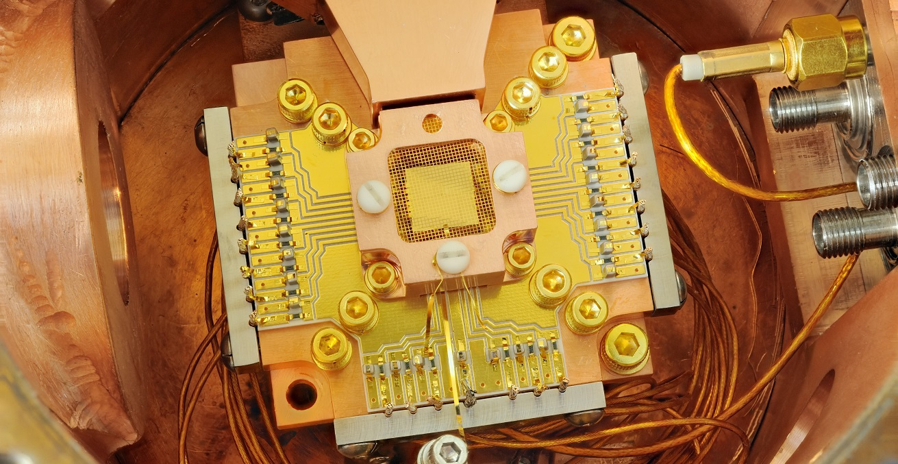 An apparatus to coax two beryllium ions (electrically charged atoms) into swapping the smallest measurable units of energy back and forth, a technique that may simplify information processing in a quantum computer. The ions are trapped about 40 micrometers apart above the square gold chip in the center. The chip is surrounded by a copper enclosure and gold wire mesh to prevent buildup of static charge. Source: Y. Colombe/NIST https://bit.ly/2XMIwfU