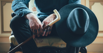 Man sitting on chair holding hat and cane. Source: https://pxhere.com/en/photo/1020358