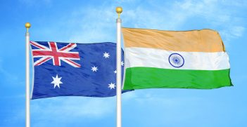 Australian and Indian flags on flagpoles with a blue cloudy sky background. Credit: Alex Shutter/Shutterstock.com