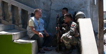 A peacebuilder with Nonviolent Peaceforce talks with two AFP soldiers. Source: Nonviolent Peaceforce https://bit.ly/3fubPcS