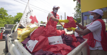 ICRC workers wearing masks distribute supplies from a truck. Source: ICRC
