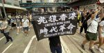 A protester holds a sign saying