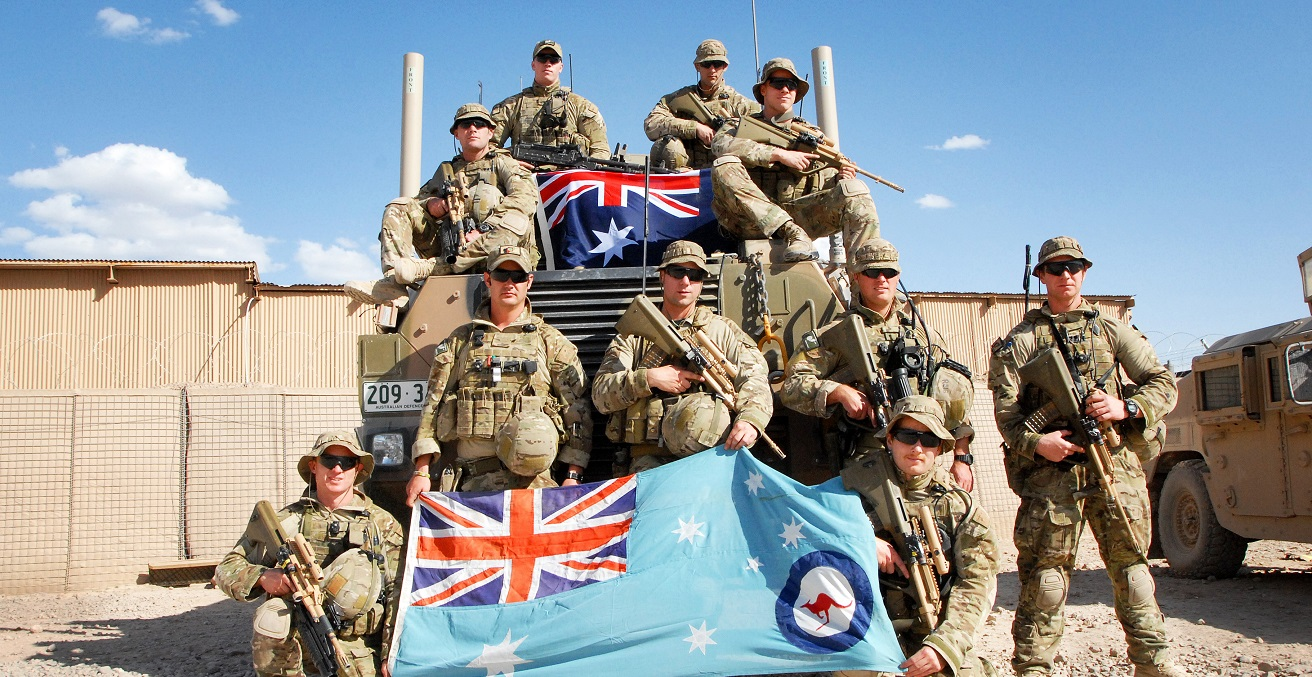 Royal Australian Air Force security force members pose with the RAAF ensign (bottom) and Commonwealth of Australia flag at Multinational Base Tarin Kot, Afghanistan. Source: U.S. Army photo by Sgt. Jessi Ann McCormick https://bit.ly/2ZM8CiK