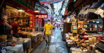 A man in a mask walks through a Guangzhou market. Source: EFE/EPA/Alex Plaveski https://bit.ly/2NJPrjW