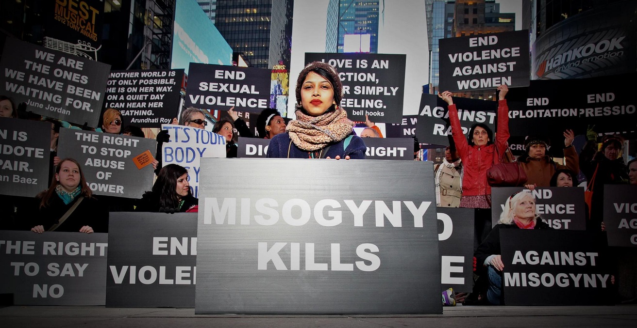 A woman holds a sign that says