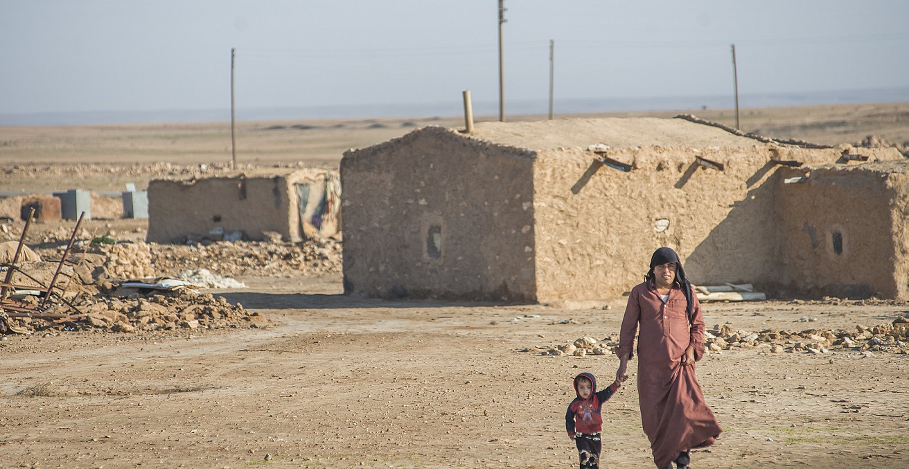 A man and child walkng across a sandy landscape in Syria. Source: Peter Biro https://bit.ly/2WHtzdQ