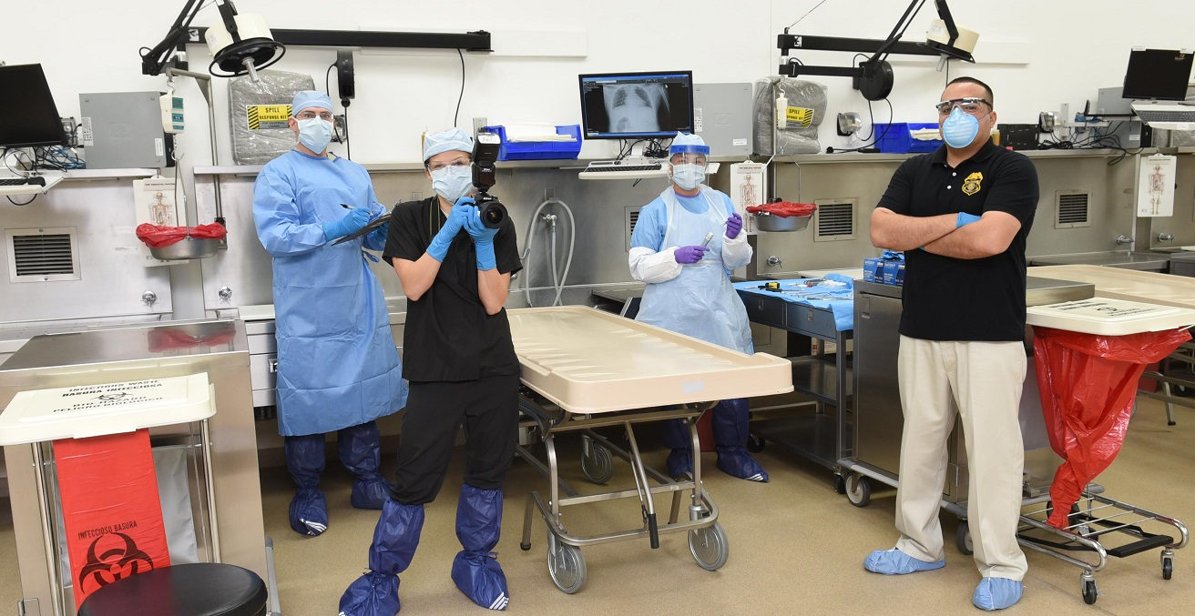 Office of the Armed Forces Medical Examiner personnel pose for a photo in the autopsy suite at the Armed Forces Medical Examiner System on Dover Air Force Base in Delaware, USA. Source: U.S. Navy photo/Mass Communication Specialist 2nd Class Samantha Thorpe https://bit.ly/2XWuLuo