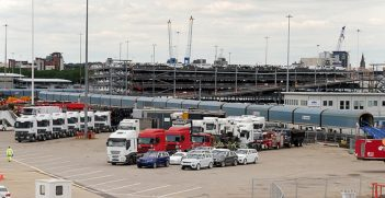 The vehicles on the quayside are waiting to be loaded onto SU4209 : Höegh America Loading Vehicles at Southampton Docks. The train behind the wharf is also full of left-hand drive cars and one of the multi-storey holding compounds can be seen behind the train. Source: David Dixon, https://bit.ly/3lpuee0