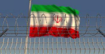Blurred waving flag of Iran behind barbed wire fence, representing imprisonment.  Source: Novikov Aleksey, https://shutr.bz/30FD7YG