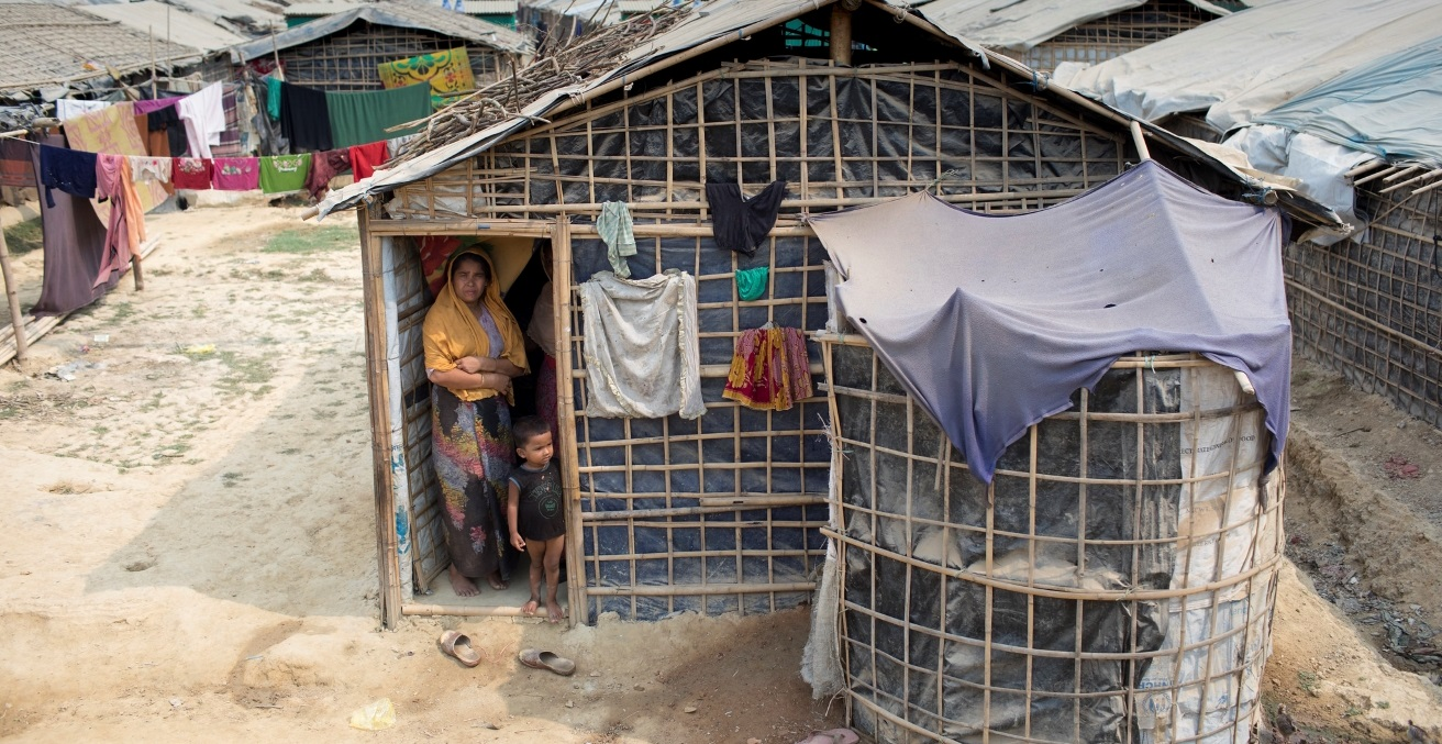 A refugee mother with her child in front of her bamboo and plastic shelter at Jadimura settlement. Source: European Union https://bit.ly/3mS3nb9