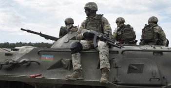 Flag of Azerbaijan on an armored personnel carrier and soldiers with machine guns. Source: Shutterstock.
