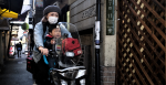 People riding a motorbike through the streets of Japan. Source: John Doe https://bit.ly/3sAdy84