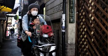 People riding a motorbike through the streets of Japan. Source: John Doe https://bit.ly/3sAdy84