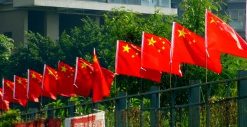 A row of Chinese flags on a fence. Source: Chris https://bit.ly/3aSUpXP