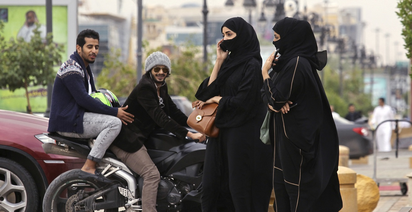 A woman speaks on the phone as men ride a motorcycle on a cloudy day in Riyadh November 17, 2013. Source: Jess Pink https://bit.ly/3qAuER0