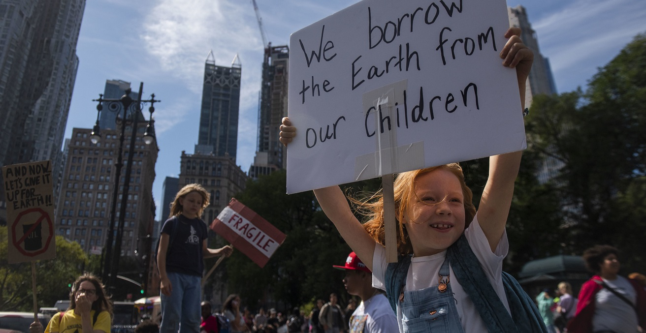 A young person holds a sign saying