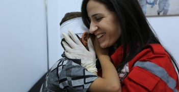 A Syrian Arab Red Crescent volunteer holds a boy after treating his injures. Source:  ICRC/Ibrahim Malla https://bit.ly/2SDP6oy