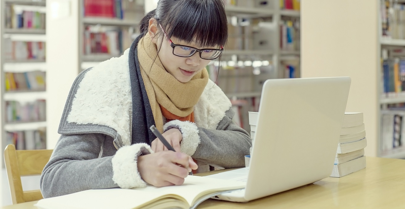 Chinese girl reading using a computer in the library. Source: LIUSHENGFILM/Shutterstock.