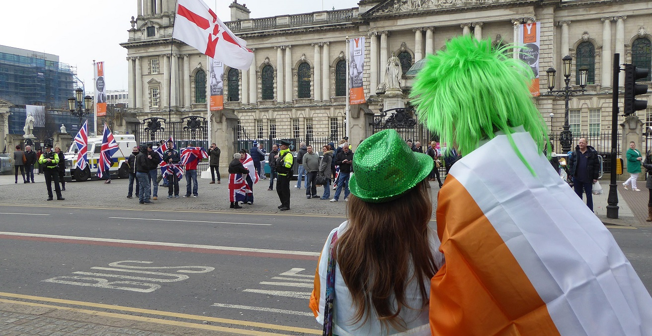 Within 40 minutes of the St Patrick's Day Parade leaving Belfast City Hall, Loyalist flag protesters appear at the same City Hall. Belfast City Hall, Belfast, Northern Ireland, March 2015. Source: Ardfern https://bit.ly/3wYIWOq