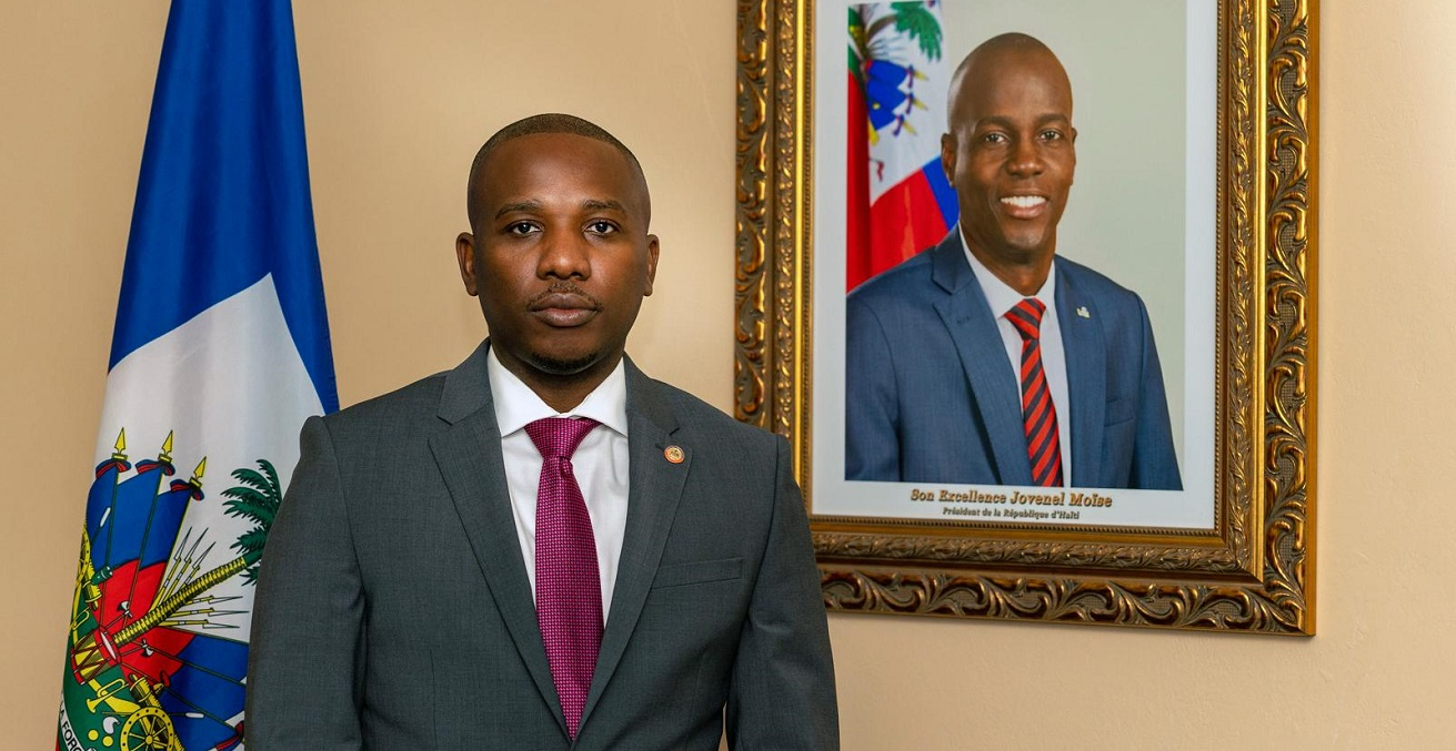 Claude Joseph stands next to a portrait of assassinated president  Jovenel Moise. Source: Rency Inson Michel https://bit.ly/3yaTjA0