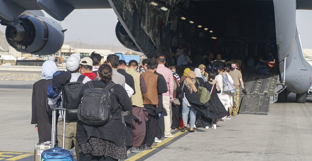 210818-M-JM820-1174 HAMID KARZAI INTERNATIONAL AIRPORT, Afghanistan (August 18, 2021) – Evacuees stage before boarding a C-17 Globemaster III during an evacuation at Hamid Karzai International Airport, Afghanistan, Aug. 18. U.S. service members are assisting the Department of State with an orderly drawdown of designated personnel in Afghanistan. (U.S. Marine Corps photo by Lance Cpl. Nicholas Guevara)