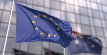 Waving flags of the EU and Australia near modern skyscraper. Source: Novikov Aleksey/Shutterstock