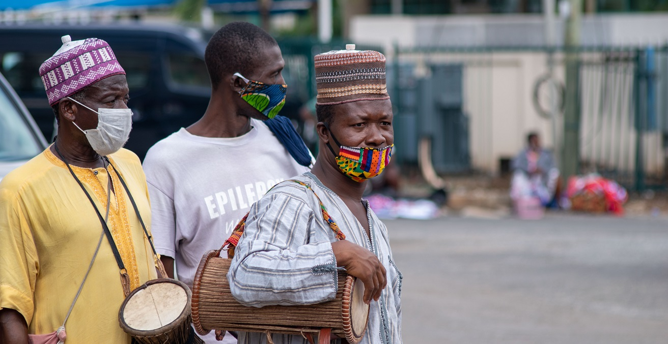 Some traditional drummers in their face masks look on in Accra, Ghana. Source: Delali92/Shutterstock